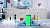 overall : POV shot of scientist holding a green screen smartphone in modern advanced research laboratory