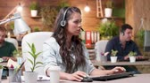 linha de apoio : Customer support operators are working in cozy office. Beautiful woman talks using the headsets Vídeos
