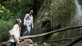oryantasyon : Slow motion shot of tourists looking up at a waterfall in the mountains Stok Video
