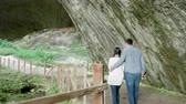 orientace : Couple looking at a cave in the mountains. Nature and travel