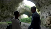 jaskinia : Couple looking at a big cave in the mountains. Nature and travel