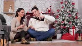 Couple drinking champagne sitting on the floor in Christmas decorated room. Romantic evening celebration. Slow motion footage