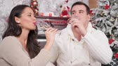 Gorgeous caucasian couple enjoying a glass of champagne in Christmas decorated room. Handheld shot