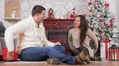 Couple giving each other presents in Christmas eve in beautiful room with a fireplace. Celebration, love and romance Stock Footage