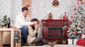 Happy inlove couple laughing and spending time together in Christmas decorated room. Love and Xmas celebration Stock Footage