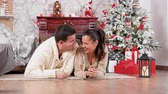Beautiful happy couple lying on the floor and drinking champagne in Christmas decorated room