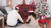 Couple in Christmas eve drinking champagne in front of a fireplace. Celebration and holiday