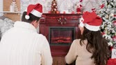 Happy couple spending Christmas in front of a fireplace, drinking champagne, selective focus Stock Footage