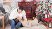 Relaxed couple lying on the floor next to a fireplace in Christmas eve with a decorated Christmas tree next