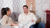Couple on the couch talking to each other and having a great time in Christmas decorated room