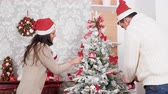 Couple decorating a Christmas tree in the living room