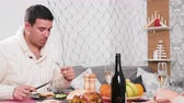 Man eating at Christmas dinner next to her wife
