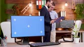 colega de trabalho : Pc monitor with green screen on office desk. Colleagues talking in the background. Stock Footage