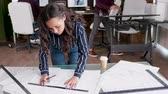 blauwdruk : Young female architect drawing line on blueprints in the office.
