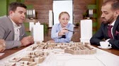 blauwdruk : Team of architects discussing about new real estate project in the conference room with mini town on the desk.