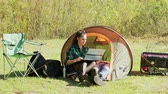 éjszakai : Beautiful young girlfriend laughing while working on her laptop in camping tent. Boyfriend relaxing while girlfriends working. Generator.