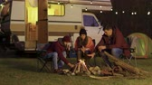 namiot : Friend of a couple helping to light the camp fire. Retro camper van. Light bulbs in the background.