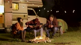 gitara : Man singing a song on guitar for his friends around camp fire in a cold night of autumn in the mountains. Retro camper van. Light bulbs.
