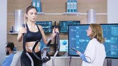 herzfrequenz : Female doctor in sport science testing woman athlete endurance in fitness centre. Female athlete running with electrodes attached to her body. Videos
