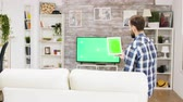 socialisation : Back view of young man sitting on couch and holding tablet with green screen. Vidéos Libres De Droits