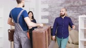 в помещении : Man from delivery service arriving with suitcases of young couple in their new real estate. Couple moving in a new apartment. Стоковые видеозаписи