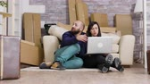 vloer : Couple sitting on the floor of new apartment and using laptop for online shopping.