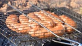 準備 : The grill with sausages is being turned around over the fire closeup