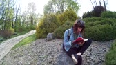 kniha : Beautiful girl reading a book while sitting on a rock in a park 2