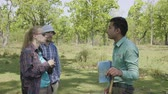 CHITWAN, NEPAL - MARCH, 2018: Nepalese guide talks to european tourists about jungle flora and fauna.