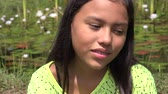 sonhar acordado : Young Girl Daydreaming near Pond Stock Footage