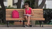 caderno : Female Student Sitting On Park Bench Drawing In Notebook Stock Footage