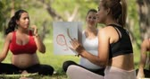 baba : Pregnant women, group of moms, mothers during pregnancy. Prenatal lesson in city park, antenatal class outdoor. Teacher, midwife, counselor, doctor teaching and explaining baby body parts. Slow motion