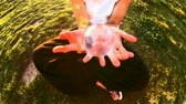 coringa : a girl plays contact juggling with a glass transparent ball