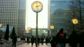 financial : timelapse of crowds walking in london docklands with big clocks telling the time