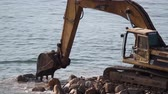 puerto vallarta : a jcb moving rocks on a beach in mexico