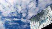 commute : reflections of clouds moving in glass mirrored office tower Stock Footage