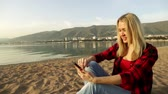 cellular : Young woman enjoys a smartphone on the background of the sea.