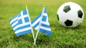 football field : Flag of Greece and soccer ball. Greek flag and ball on the grass.