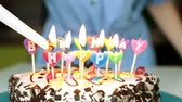 koláč : A woman lights candles on a cake. Birthday, holiday and cake with candles. Dostupné videozáznamy