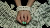 Bound hands against the background of dollars.