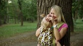 potomstvo : A woman with a child in a sling speaks on a smartphone