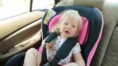 seat belts : child is traveling in the car. A small child is sitting in a car seat. Stock Footage