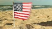 полосы : Flag of the United States on the beach. American flag on the sandy beach.