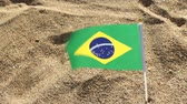 işareti ok : Flag of Brazil on a sandy beach.