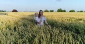 Aerial view - woman with a child walking on a wheat field.