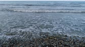perspective view : Rocky sea shore, sea waves, beach, surf. Slow motion.
