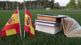 keménytáblás : Spanish language and education. Flag of Spain and books on the grass.