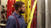 comparar : Bearded man in a hardware store chooses a building level.