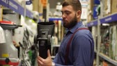 home improvement : Brutal man with a beard in a hardware store chooses tools. Stock Footage
