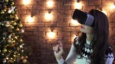 simulatie : A young woman in VR glasses makes gestures with her hands. New year and Christmas. Stockvideo